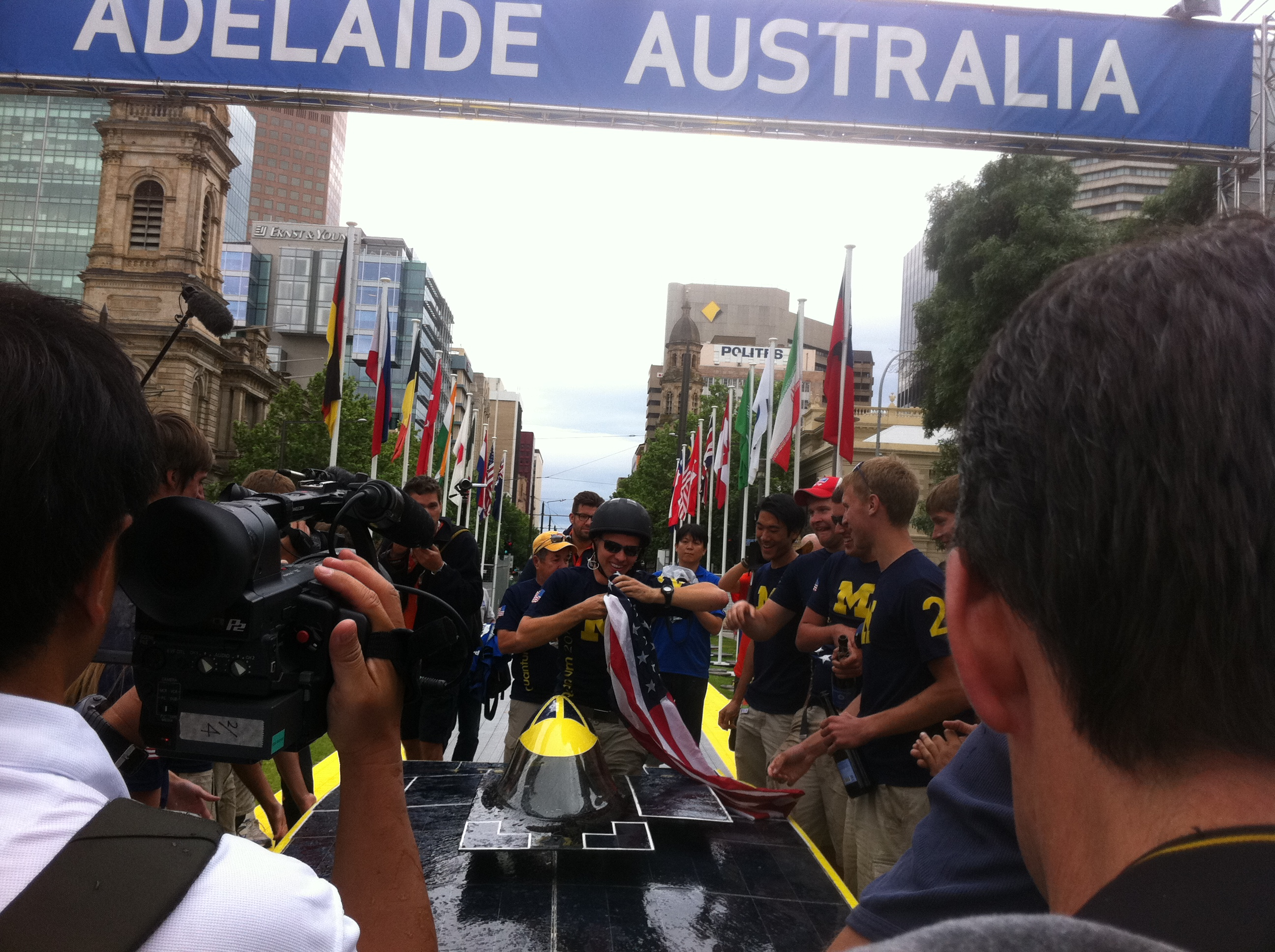 Quantum driver welcomed by team members as one of the top three winning teams arriving at Victoria Square of Veolia World Solar Challenge 2011