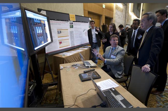SunShot Energy Secretary Steven Chu looks at new technology with exhibitor Joe Sarubbi, seated (Creative Commons)
